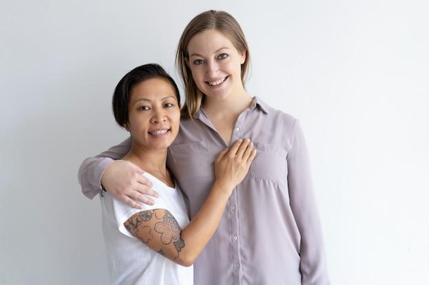 Feliz pareja de lesbianas multiétnica abrazando