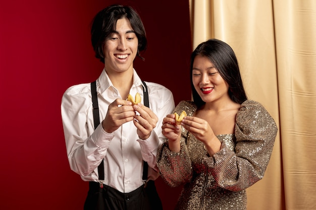 Feliz pareja leyendo el mensaje de la galleta de la fortuna para el año nuevo chino
