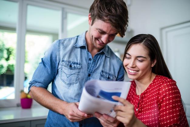 Feliz pareja leyendo periódico en casa