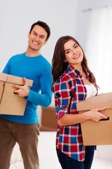 Feliz pareja llevando cajas en su nuevo hogar