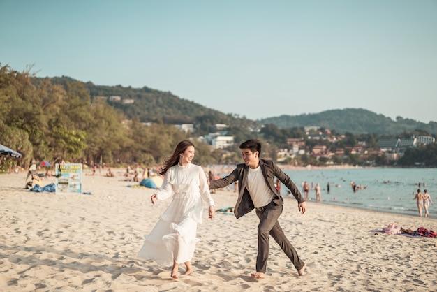 Feliz pareja va de luna de miel a viajar en la playa de arena tropical en verano