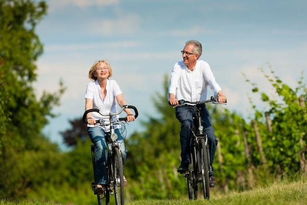 Feliz pareja madura andar en bicicleta en la naturaleza