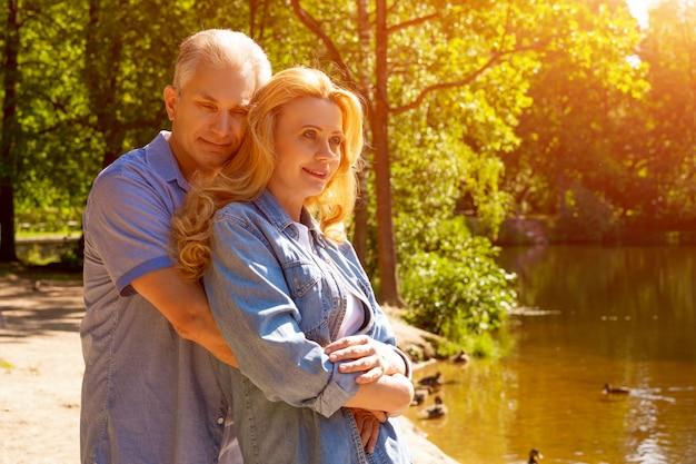 Feliz pareja madura de pie en un abrazo en el lago en el sol