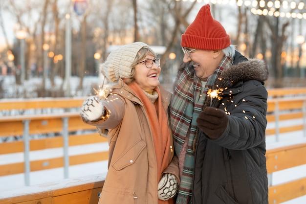 Feliz pareja madura sosteniendo estrellitas y sonriendo el uno al otro que celebran la navidad en el parque