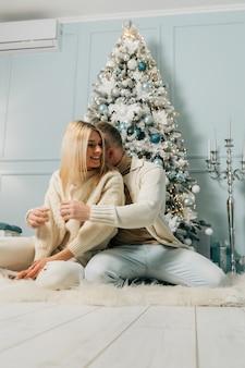 Feliz pareja, marido y mujer están sentados cerca de un árbol de navidad decorado en nochebuena. año nuevo y vacaciones de navidad