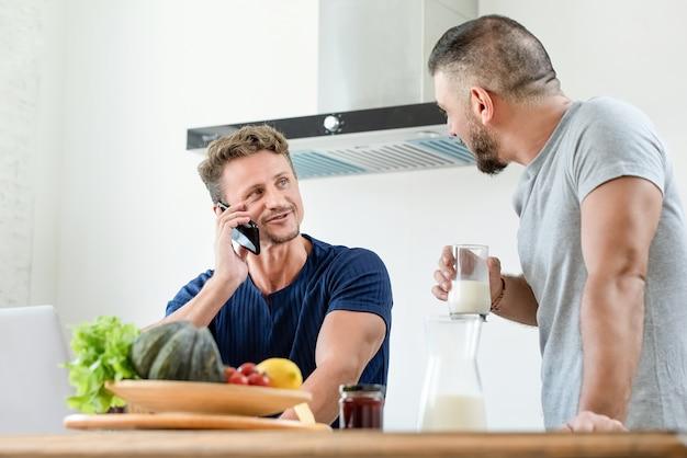 Feliz pareja masculina gay en casa por la mañana