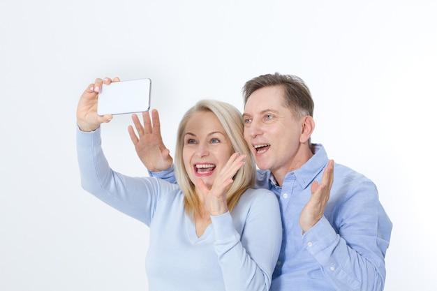 Feliz pareja de mediana edad tomando selfie con smartphone aislado en blanco