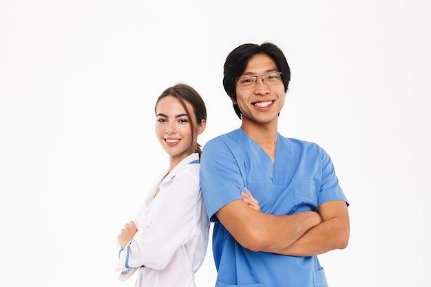 Feliz pareja de médicos vistiendo uniforme que se encuentran aisladas sobre una pared blanca, con los brazos cruzados