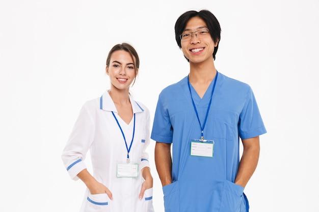 Feliz pareja de médicos vistiendo uniforme que se encuentran aisladas sobre pared blanca