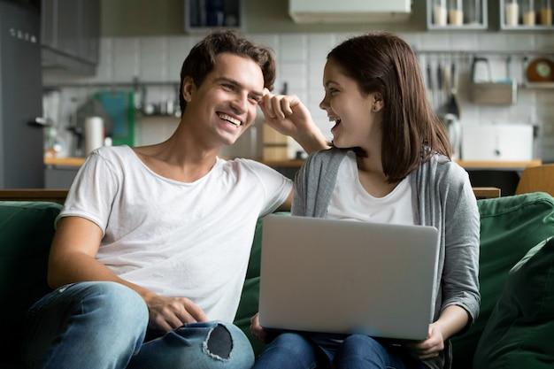 Feliz pareja milenaria riendo usando laptop juntos en el sofá de la cocina