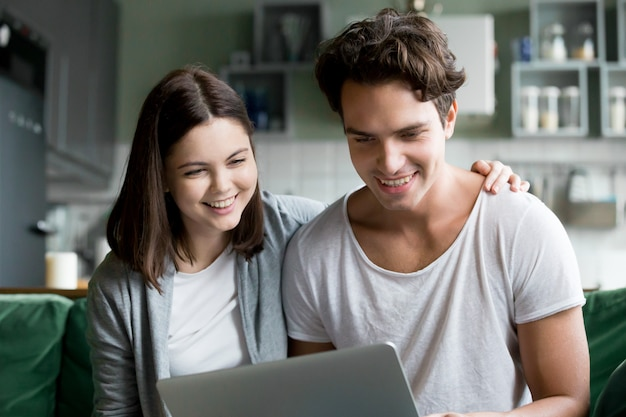 Feliz pareja milenaria sonriendo mirando la pantalla del portátil haciendo videollamada