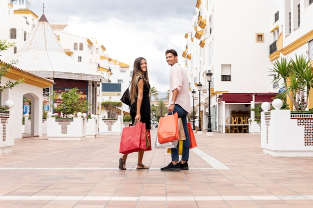 Feliz pareja mirando hacia atrás con bolsas