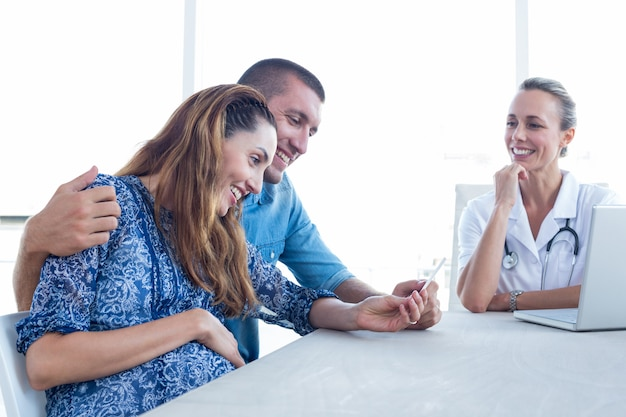 Feliz pareja mirando ecografía de su bebé