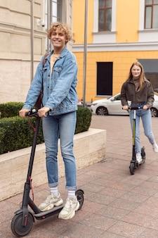 Feliz pareja montando scooters eléctricos en la ciudad