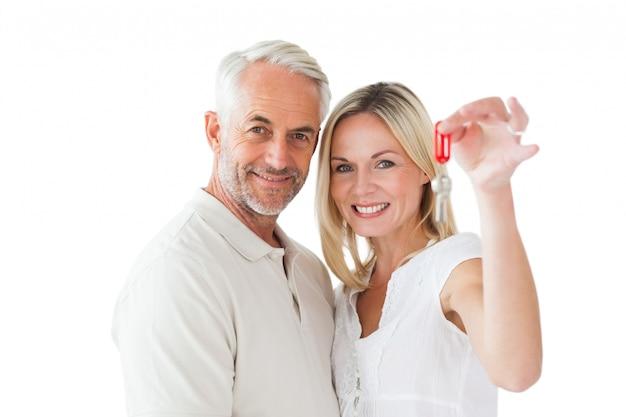Feliz pareja mostrando su nueva llave de la casa