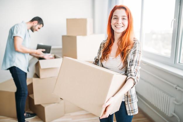 Feliz pareja mudarse a casa nueva. hombre y mujer desembalaje de cajas de cartón, inauguración de la casa