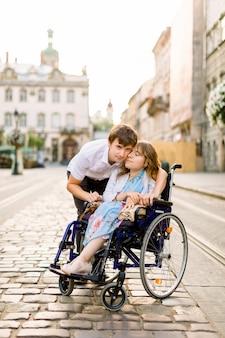 Feliz pareja con mujer discapacitada caminando en la ciudad vieja