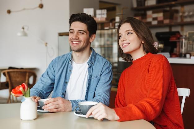 Feliz pareja mujer y hombre sonriendo y mirando a un lado, mientras descansa en la cafetería y bebe café o té juntos