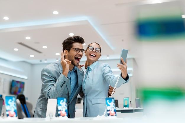 Feliz pareja multicultural vestida con ropa de negocios tomando selfie con nuevo teléfono inteligente mientras está de pie en la tienda de tecnología
