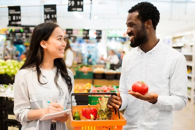 Feliz pareja multiétnica elegir productos en supermercado
