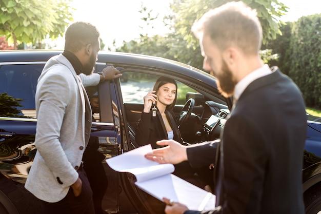 Feliz pareja multiétnica, hombre africano y mujer caucásica, comprando el automóvil, crossover negro, mujer sentada en el automóvil y sosteniendo las llaves del automóvil. joven vendedor tiene carpeta con contrato de venta