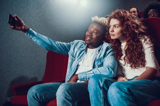Feliz pareja multiétnica toma selfie en cine