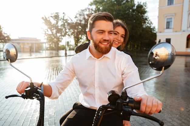 Feliz pareja de negocios monta en moto moderna en el parque