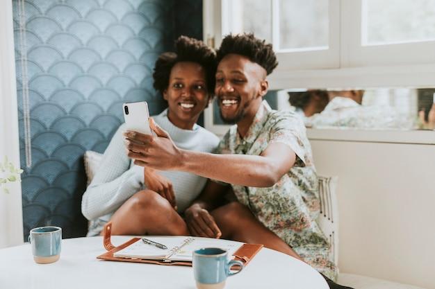 Feliz pareja negra tomando un selfie en casa con un móvil