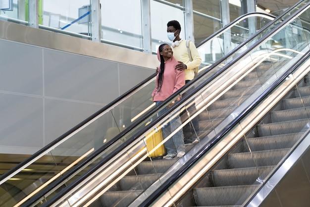 Feliz pareja negra viaja en covid lockdown hombre negro en máscara médica abrazo mujer sosteniendo maleta