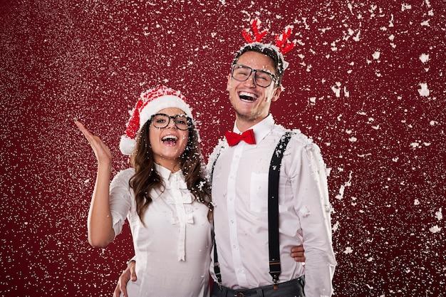 Feliz pareja nerd rodeada de copos de nieve