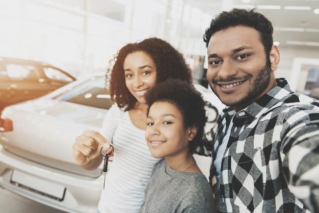 Feliz pareja y niño toman selfie con las llaves del coche.
