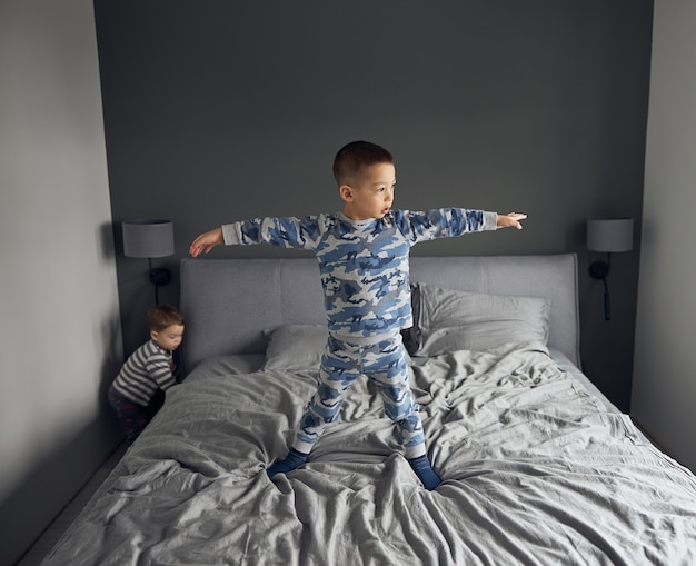 Feliz pareja de niños jugando en el dormitorio acogedor