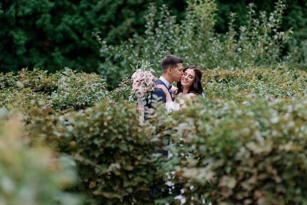 Feliz pareja de novios está sonriendo y besándose en los altos arbustos verdes