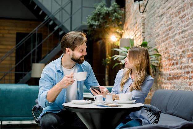 Feliz pareja o amigos coqueteando hablando y bebiendo café en un restaurante o cafetería o sala de espera