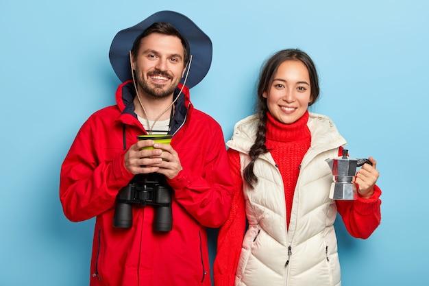 Feliz pareja pasa el fin de semana en la naturaleza, toma café, disfruta del aire fresco, usa binoculares, se viste con ropa informal abrigada, se para uno al lado del otro sobre una pared azul