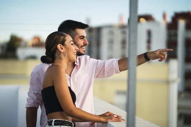 Feliz pareja de pie en el balcón y pasar un rato romántico juntos