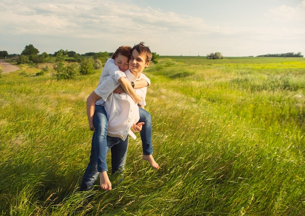 Feliz pareja de pie en el campo al atardecer
