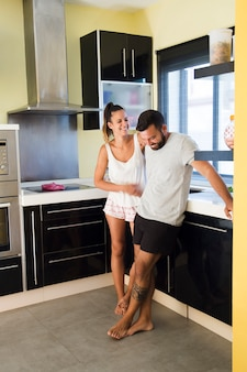 Feliz pareja de pie en la cocina moderna