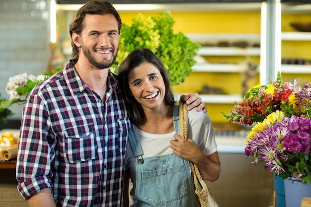 Feliz pareja de pie en la floristería