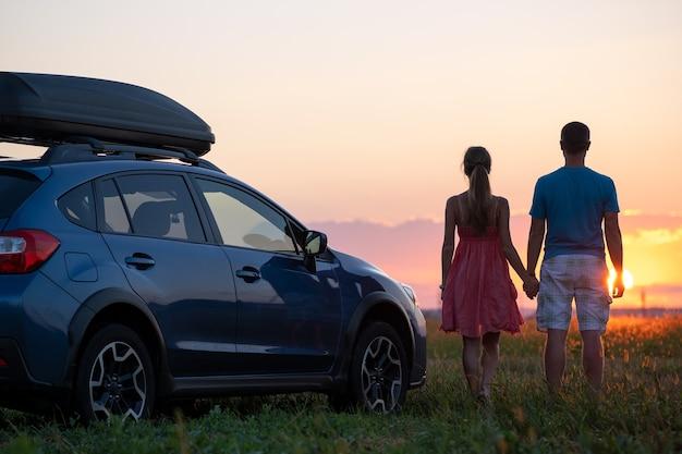 Feliz pareja de pie junto a su coche suv durante el viaje por la noche.