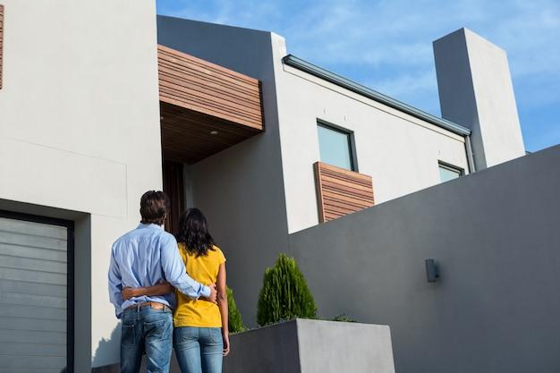 Feliz pareja de pie y mirando la nueva casa