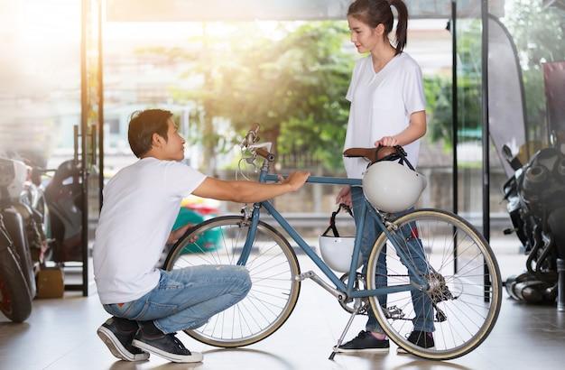 Feliz pareja de pie y revisando la bicicleta en casa antes de viajar