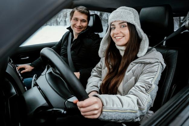 Feliz pareja posando juntos en el coche durante un viaje por carretera