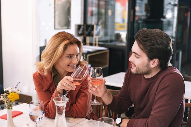 Feliz pareja positiva bebiendo vino y hablando