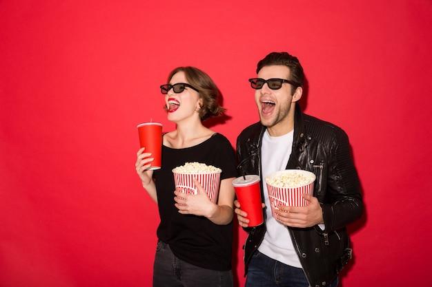 Feliz pareja punk en anteojos con refrescos y palomitas de maíz