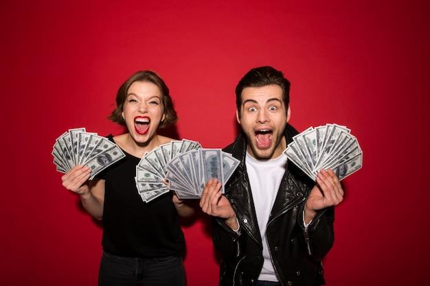 Feliz pareja punk gritando posando con dinero y regocijarse