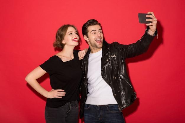 Feliz pareja punk posando y haciendo selfie en smartphone