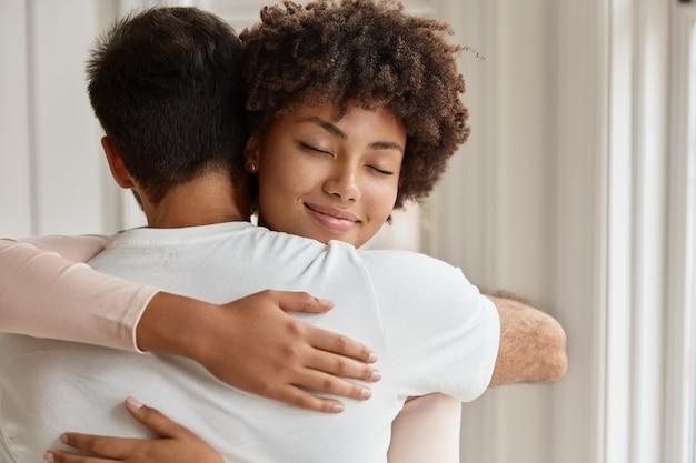 Feliz pareja de raza mixta tiene un cálido abrazo