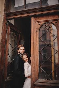 Feliz pareja de recién casados abrazándose y besándose en la vieja calle de la ciudad europea