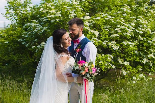 Feliz pareja de recién casados besándose en el jardín verde